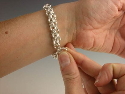Puting the chain maile bracelet on by Kate Wilcox-Leigh